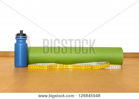 Centimeter tape yoga mat and bottle of water for exercise on yellow background. Equipment for yoga.