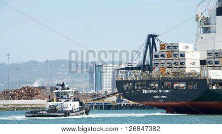 Tugboat Z-five At The Stern Of Cargo Ship Seaspan Ningbo