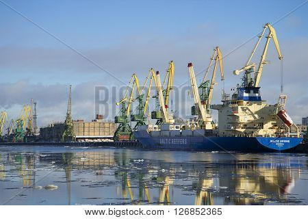 ST. PETERSBURG, RUSSIA - FEBRUARY 17, 2016: February sunny day at Kanonersky channel. Cargo cranes loading barges with cargo in big port of St. Petersburg