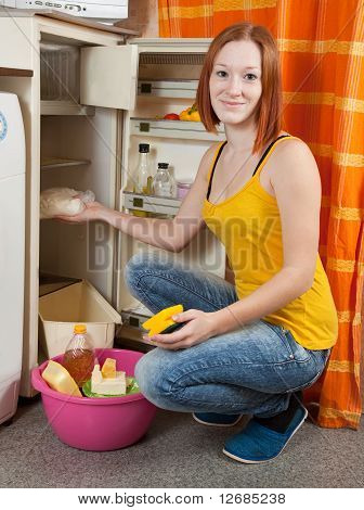 Woman  Defrosting The Refrigerator