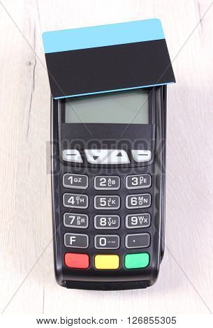Credit card reader payment terminal and contactless credit card on wooden background cashless paying for shopping or products