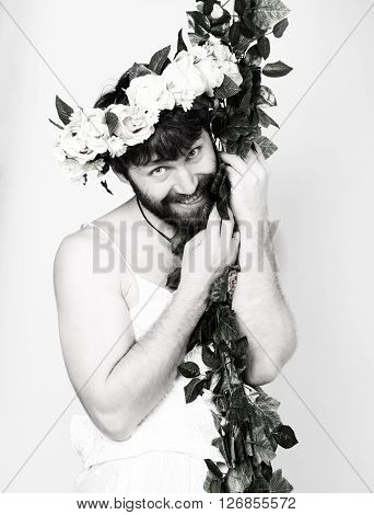 bearded man in a woman's wedding dress on her naked body, clinging to the vine. on his head a wreath of flowers. funny bearded bride, black and white.