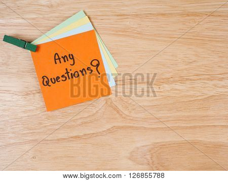 Handwriting spell Any Questions on colorful note paper with wood background