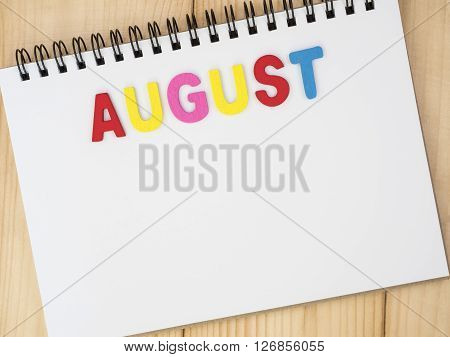 Word spelling month in the year August by wooden letters on notebook with wood background (Month name word series)