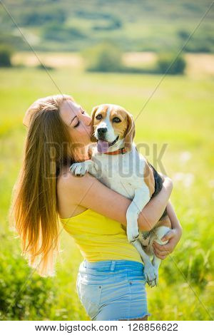 Teenage girl kissing her beagle dog - outdoor in nature