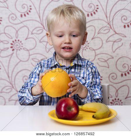 The three-year boy eats a yellow grapefruit at home