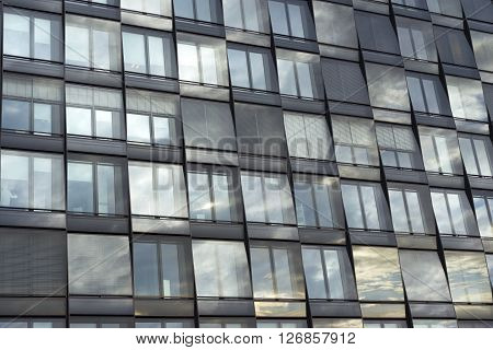 window pattern of modern city building with dark gloomy sky reflection