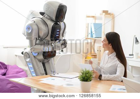 Do you need my help. Nice delighted woman sitting at the table and using tablet while talking with robot who is standing nearby