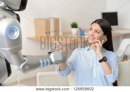 Nice gesture. Cheerful delighted beautiful girl sitting at the table and talking on cell phone while getting glass of water from the robot