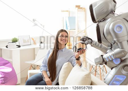 Nice device. Cheerful content beautiful girl sitting on the sofa and smiling while giving headphones to the robot