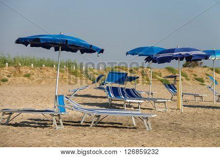 Empty deck chairs under umbrellas on the beach