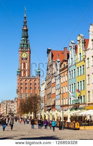 GDANSK, POLAND - APRIL 21, 2016: Street scene with renaissance building of the former Town Hall in Gdansk. Old Town in Gdansk is a tourist attraction for visitors.