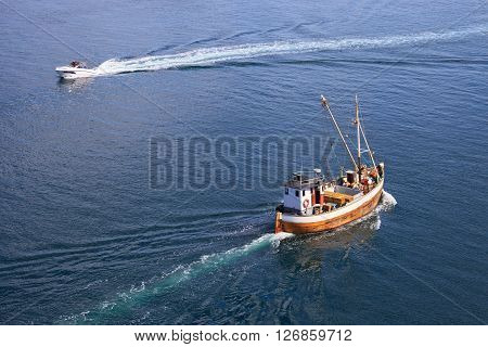 Old wooden fishing boat trawler on sea.