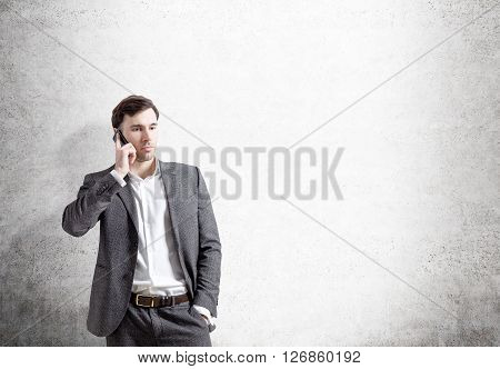 Businessman talking on the phone on concrete background. Mock up