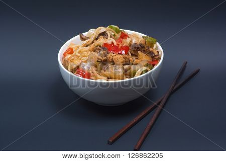 Chinese boiled noodles with a chicken and vegetables  on the black background