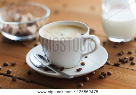 caffeine, objects and drinks concept - close up coffee cup and grains on wooden table