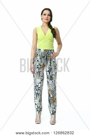 woman with straight pony tail hair style in sleeveless summer top printed casual baggy trousers high heel shoes going full body length isolated on white