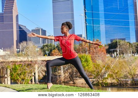 Runner girl stretching listening music earphones in the city park