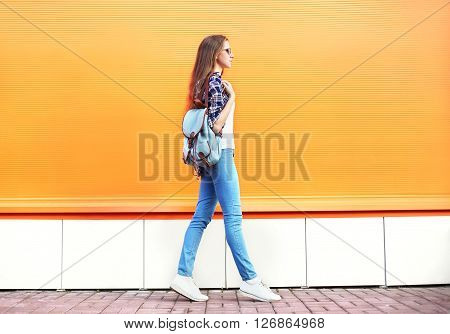 Fashion Woman Walking In City Over Colorful Orange Background