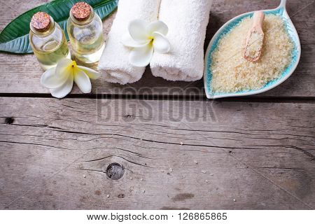 Spa setting. Sea salt in bowl in form of leaf with towels and bottles with oil on vintage wooden background. Selective focus is on towels. Place for text.