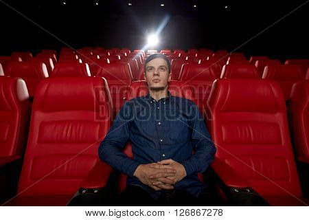 cinema, entertainment and people concept - young man watching movie alone in empty theater auditorium