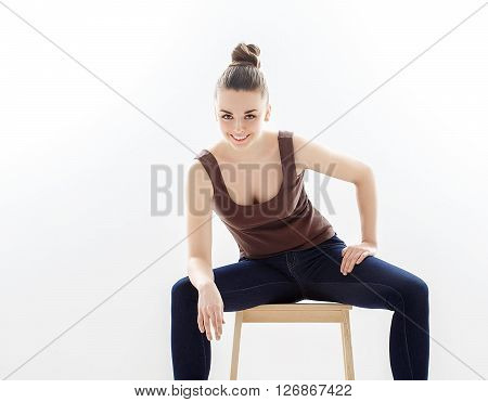 Elegant Woman Sitting On A Chair In Blue Jeans In The Studio.