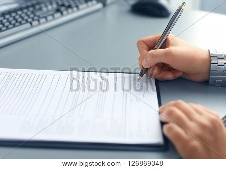 Businesswoman sitting at office desk signing a contract with shallow focus on signature.
