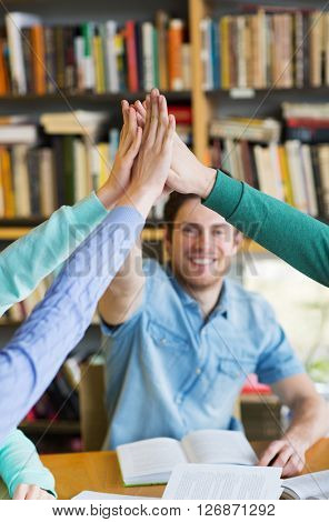 people, education and high school concept - close up of happy students making high five gesture and preparing to exam in library