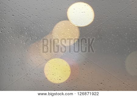 Drops of rain on gray glass with defocused city lights