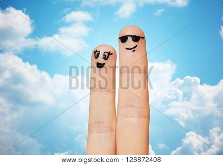 family, couple, people and body parts concept - close up of two fingers with smiley faces over blue sky and clouds background