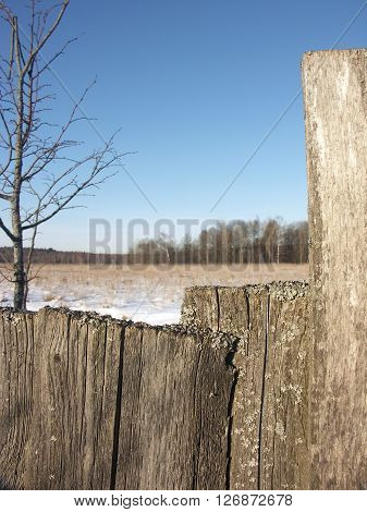Old wooden fence from boards closeup with snow on top and winter field in the background