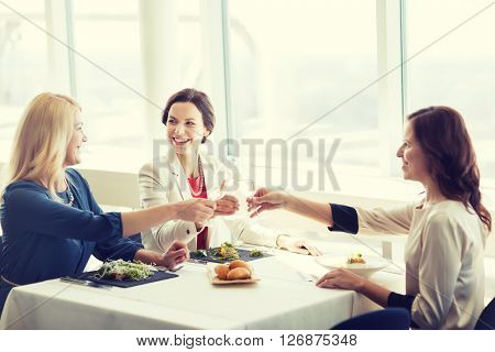 people, holidays, celebration and lifestyle concept - happy women drinking champagne and clinking glasses at restaurant