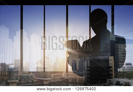 business and people concept - silhouette of business man with tablet pc over double exposure office and city background