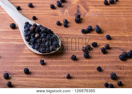 Black Peppercorn Seeds On Wooden Table