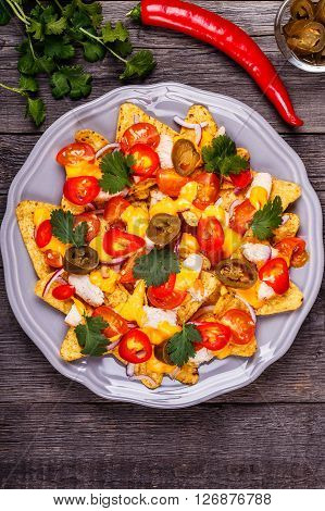 Nachos with melted cheese sauce jalapeno chicken and vegetables on dark wooden background.