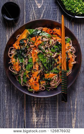 Soba noodles with vegetables and seaweed top view.