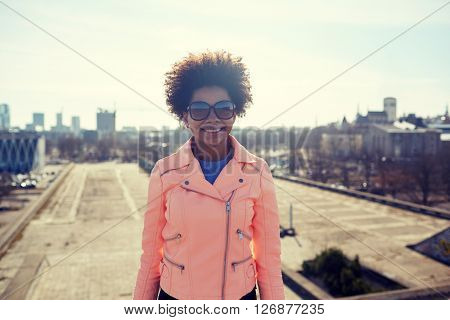 tourism, travel, people, international  and leisure concept - happy african american teenage girl or young woman in shades on tallinn city street