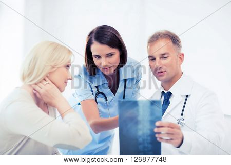 healthcare, medical and radiology concept - doctors with patient looking at x-ray