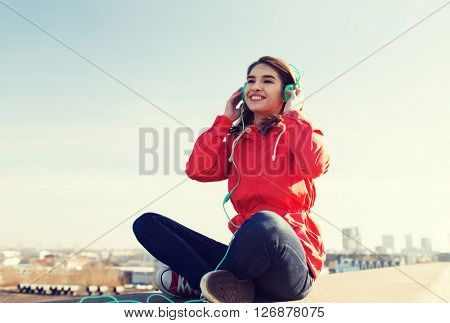 technology, lifestyle and people concept - smiling young woman or teenage girl in headphones listening to music outdoors