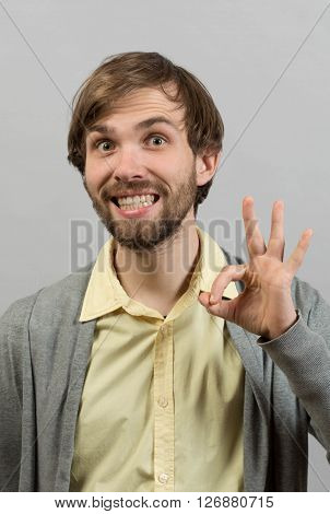 Everything is OK. Happy young man in shirt gesturing OK sign and smiling while standing against grey background