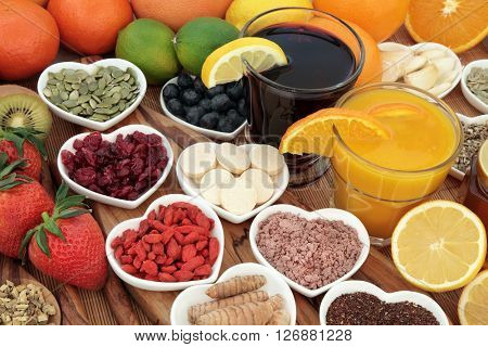 Health food for cold cure with fruit, orange and blackcurrant drinks high in antioxidants and vitamin c with supplement capsules and medicinal herbs.