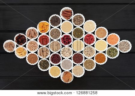 Large dried health food sampler in china bowls forming an abstract background. High in antioxidants, minerals, vitamins and dietary fiber.