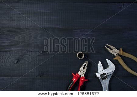 Different kinds of tools with a notebook on wooden background closeup