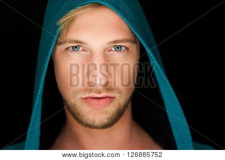 sexy young man with a hoodie close up portrait blue eyes and blonde hair