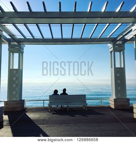 NICE - JANUARY 28: A couple sit facing the Mediterranean sea from the Promenade des Anglais on January 28, 2016 in Nice, France.