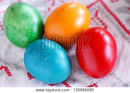 four colorful Easter eggs on linen tablecloth