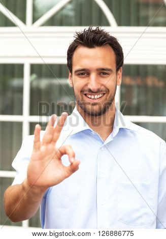 Latin business man makes compliment outdoors in front of his office