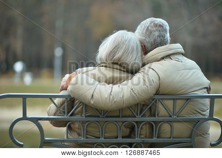 Elderly couple resting together on bench at autumn park , back view