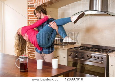 Cute couple having fun and boyfriend picking up girlfriend in the kitchen