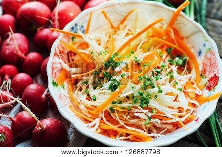 Cabbage salad. cabbage salad with sweet carrot radish bow in a white bowl. Coleslaw salad in white bowl on a brown background. fresh vegetables salad with cabbage and carrot. Rustic style